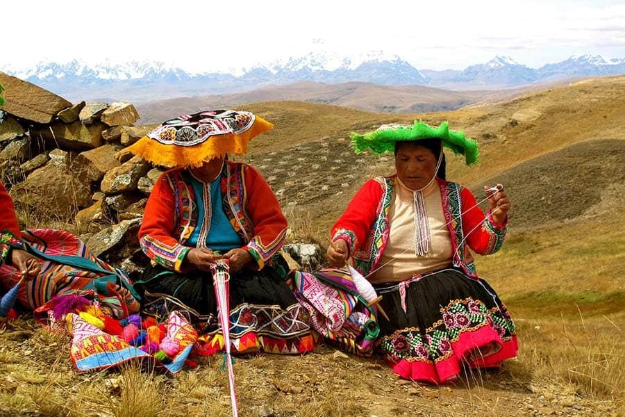 Two Peruvian women weaving colorful textiles