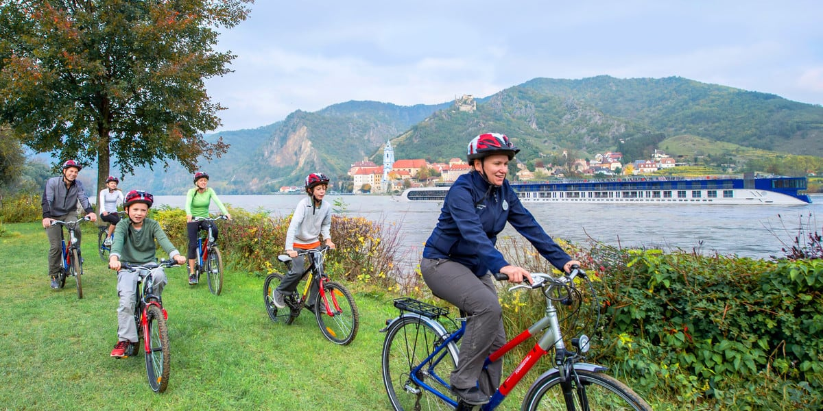 Adventures By Disney River Cruise family riding bikes by the river
