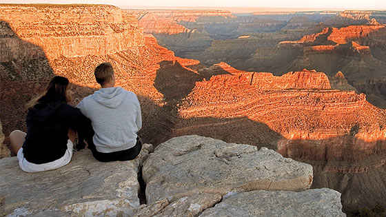 A couple sits on a rock overlooking the grand canyon