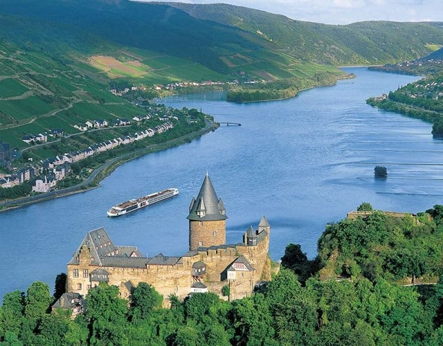 A Viking Cruise ship passes by a castle overlooking a beautiful river